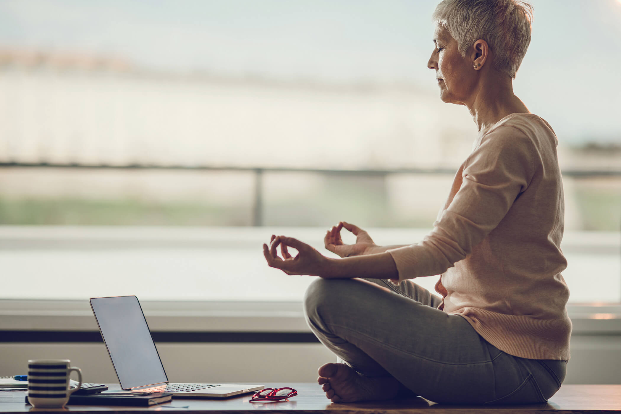 Woman doing yoga in front of her laptop, while online.