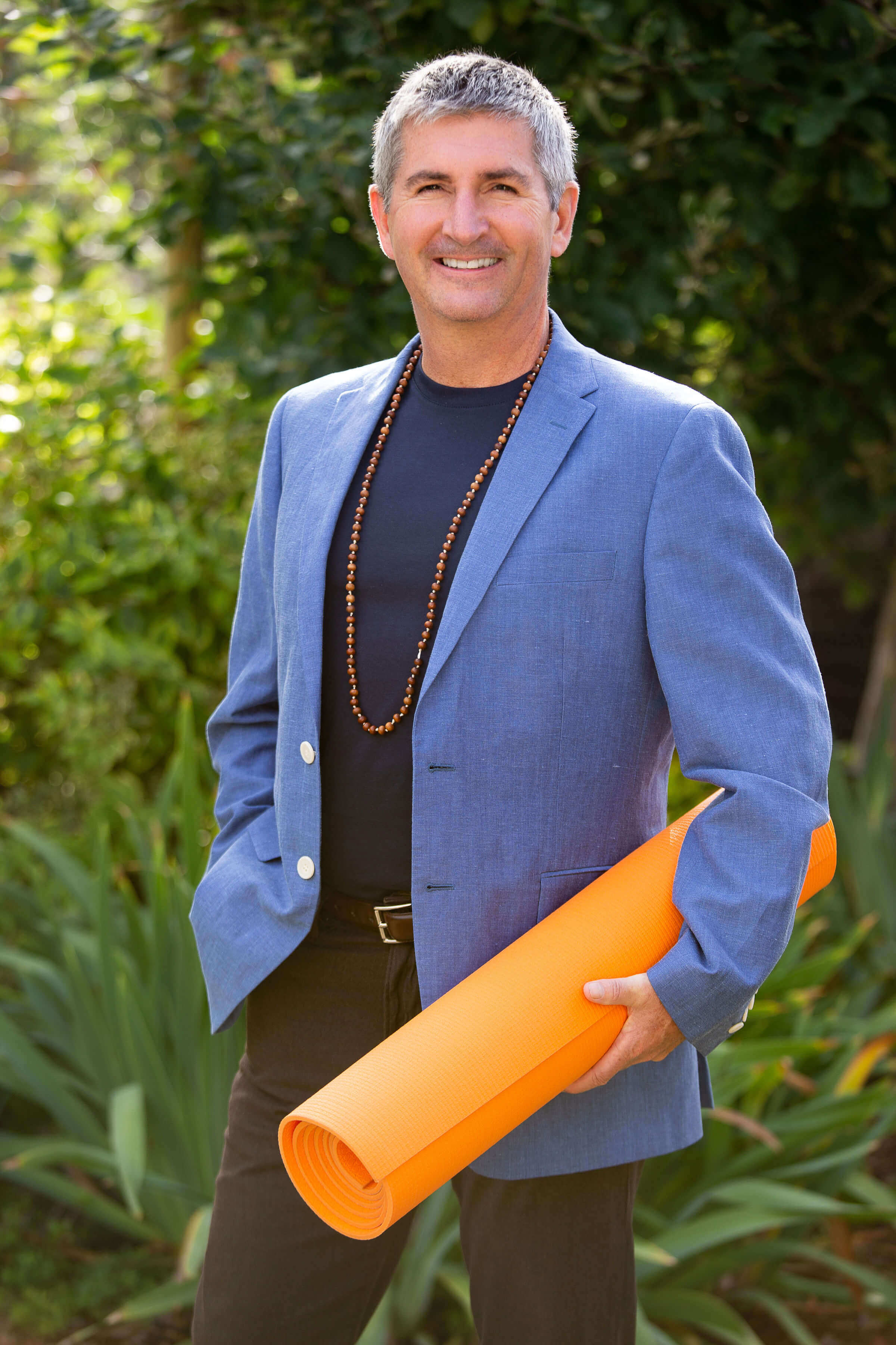 Neil Pearson in a blue jacket and shirt, with an orange yoga mat under his arm