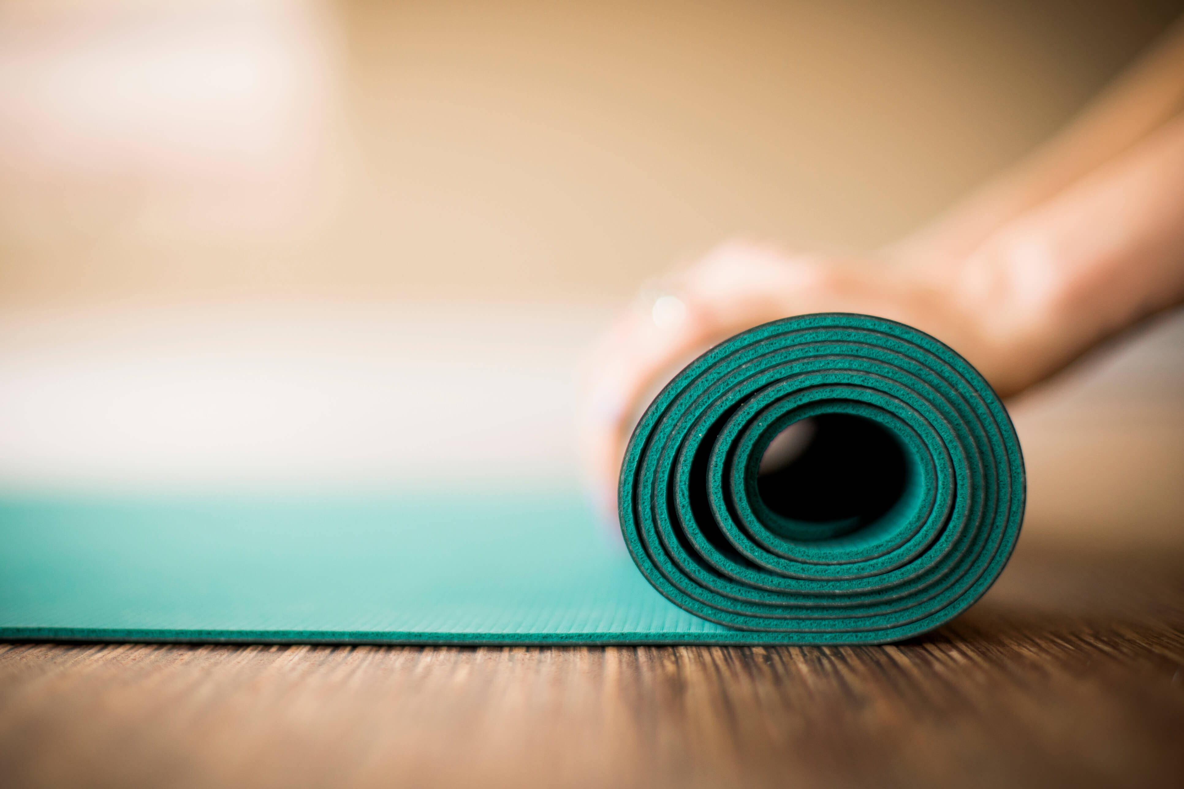 A green yoga mat being rolled out in a studio